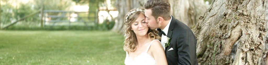 A groom kisses his bride on the cheek as they lean against a tree.