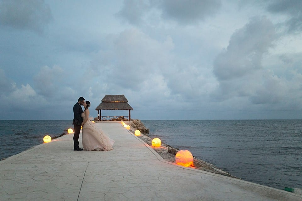 A bride and groom kiss on the pier looking into the ocean at Hotel Marina El Cid Spa & Beach Resort in Cancun, Mexico. Image by Clint Bargen Photography.