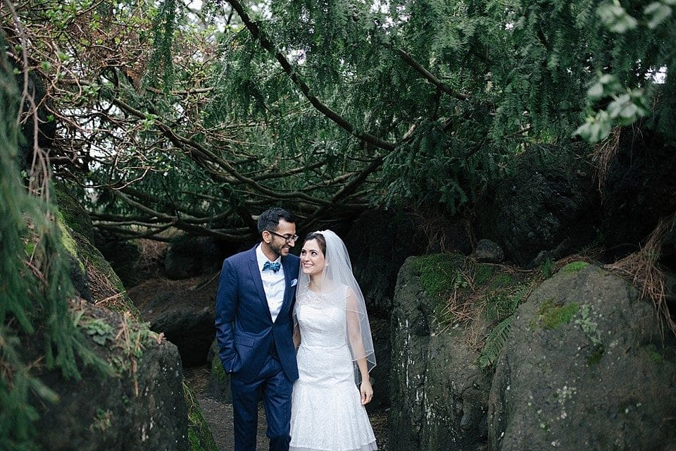 A Persian bride looks up at her Indian groom in a blue suit and smiles as they walk out from a forest and rock pile at Van Dusen Gardens in Vancouver, BC. Photo by Clint Bargen Photography.