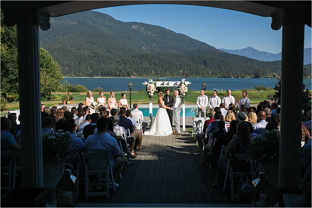 A wedding ceremony is held with the mountains, river and pool as the backdrop at Rowena's Inn on the River near Harrison Mills, BC by Clint Bargen Photography.