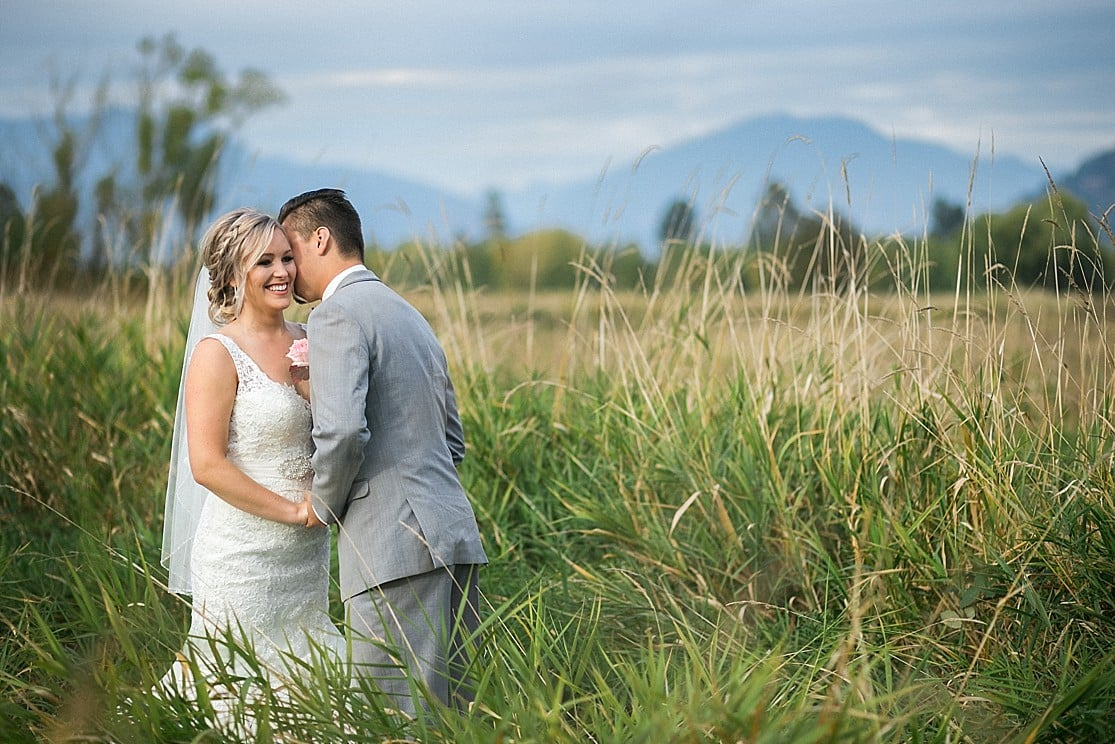 A groom kisses his bride on the cheek in Abbotsford, BC by Clint Bargen Photography.