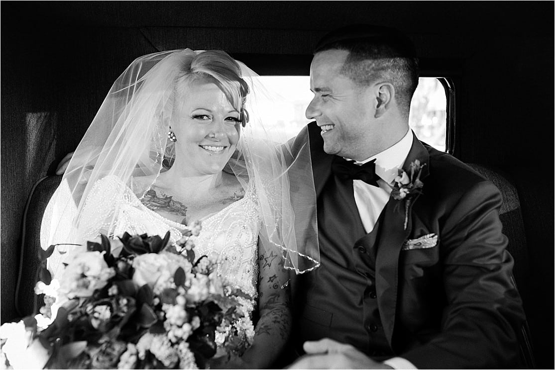 A bride and groom share a laugh in the back of a classic car by Clint Bargen Photography.