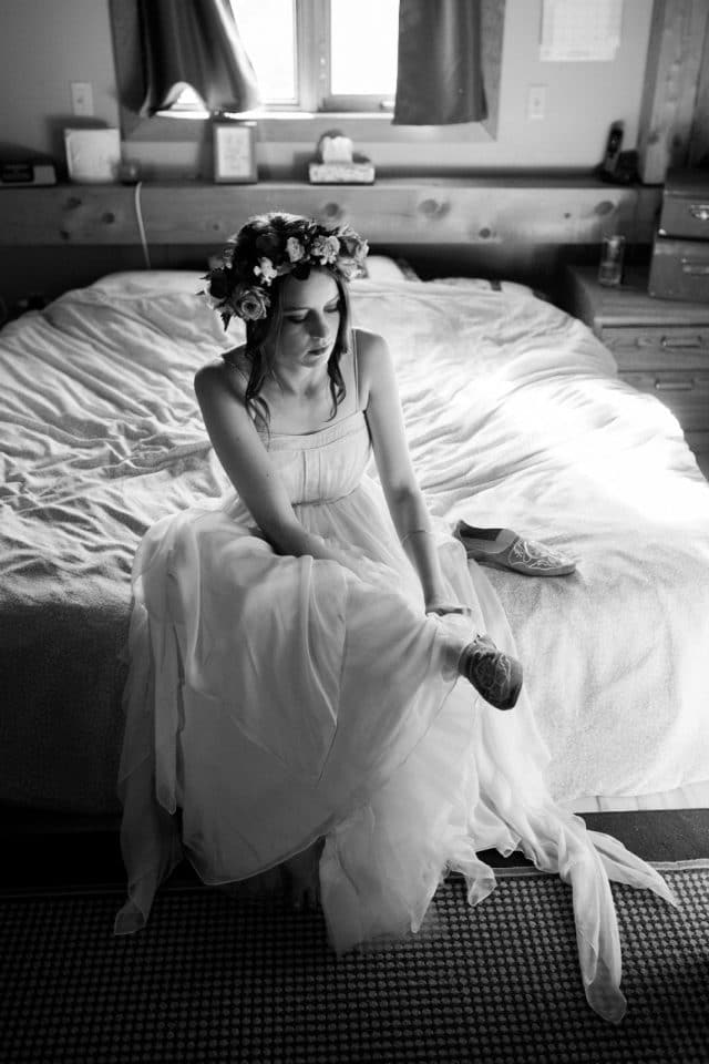 A bride puts on her shoes in a BHLDN wedding dress by Clint Bargen Photography.
