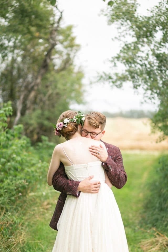 A bride in a BHLDN dress embraces her husband for the first time.