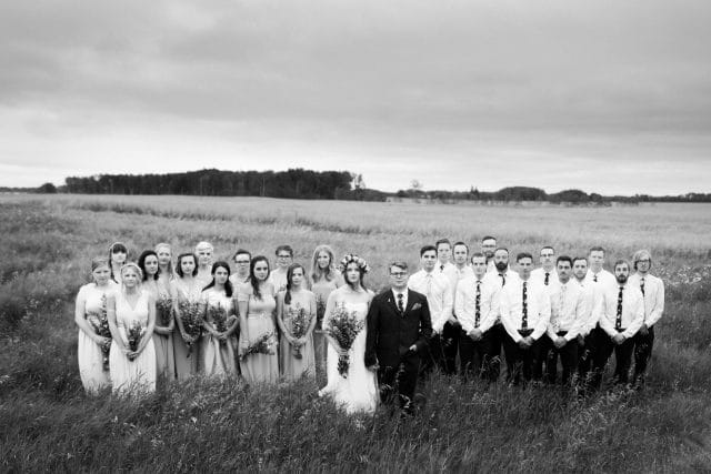 A wide shot of a bride and groom plus their 26 groomsmen and bridesmaids.
