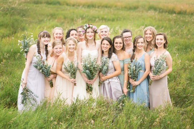 A bride stands with 13 of her best friends on her wedding day in a field of tall grass.
