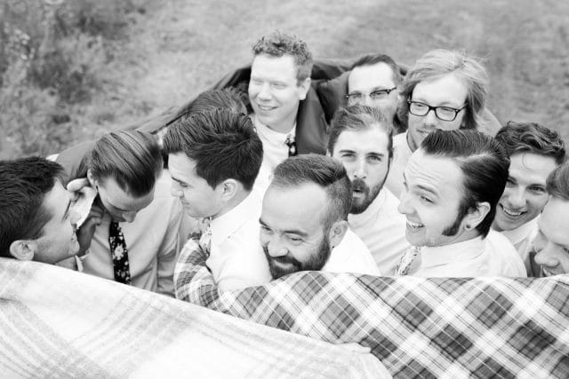 A group of 10 groomsmen huddle together for warmth in a sleeping back.