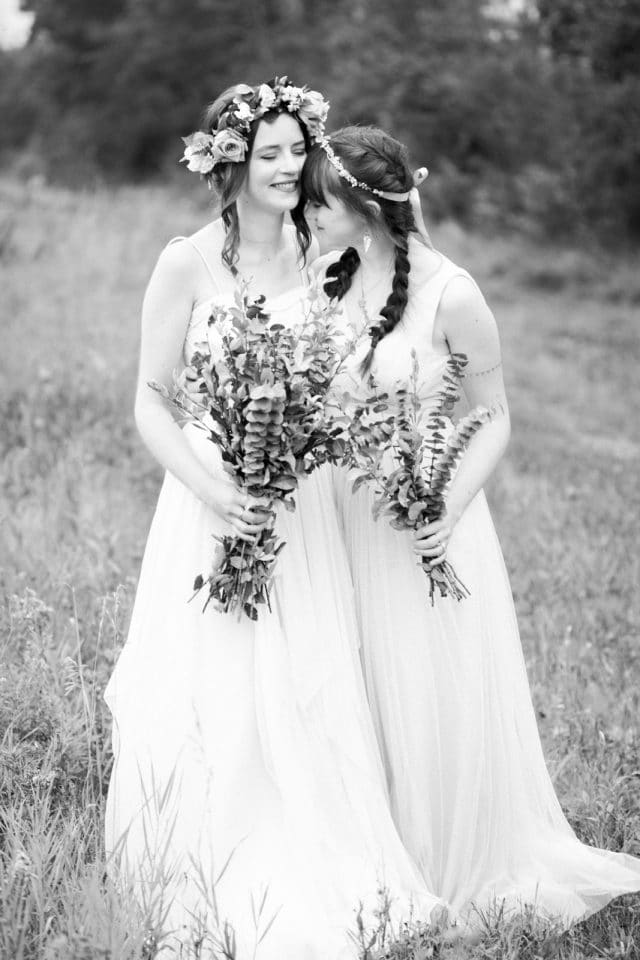 A bride embraces her sister as she stands in a field in Saskatchewan.