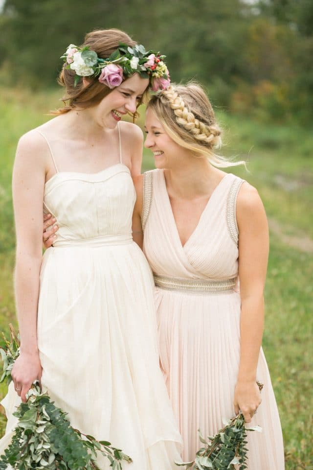 A bride laughs with one of her bridesmaids as they stand in a field.