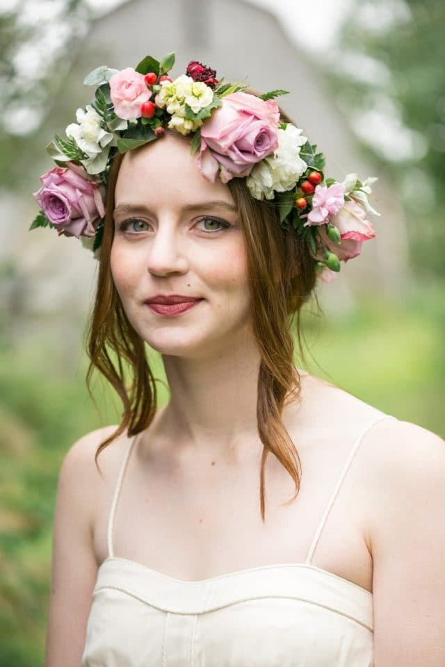 A bride looks into the camera wearing a flower crown and a BHLDN dress by Clint Bargen Photography.