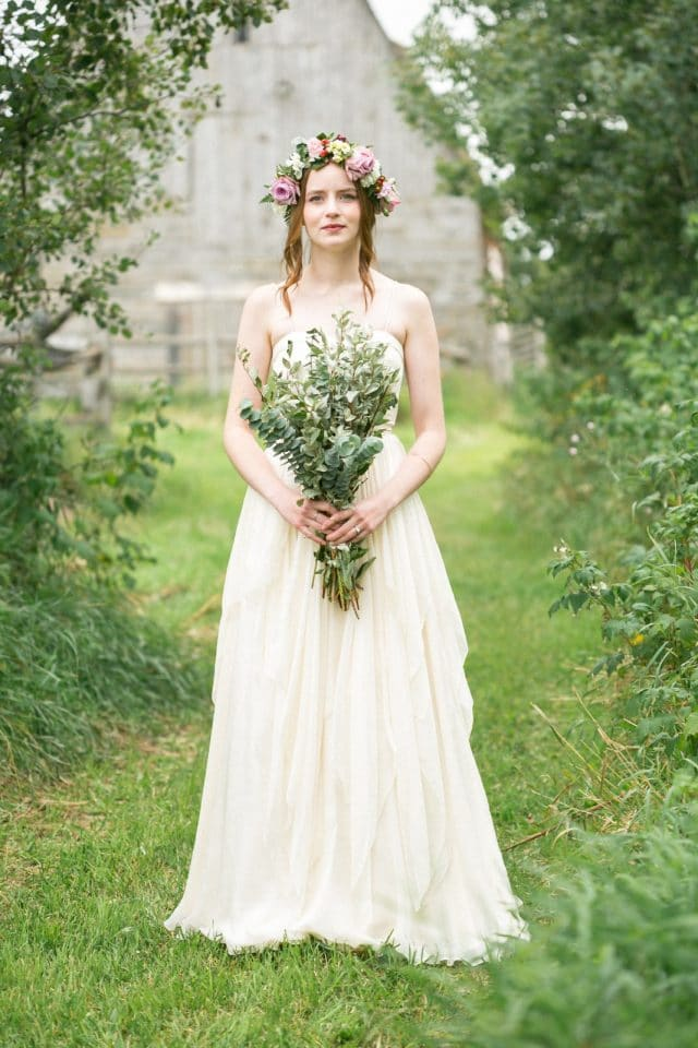 A bride stares straight into the camera wearing a BHLDN dress.