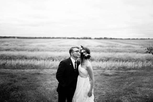 A bride and groom kiss in front of a wheat field in Glenbush, Saskatchewan by Clint Bargen Photography.
