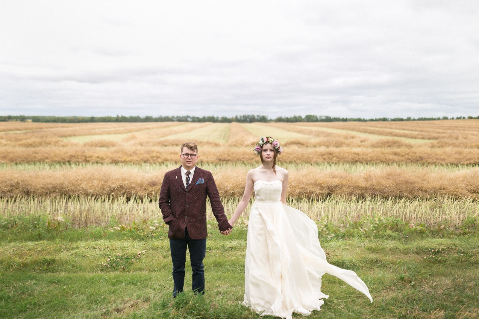 A bride and groom stand in front of a wheat field in Glenbush, Saskatchewan by Clint Bargen Photography.