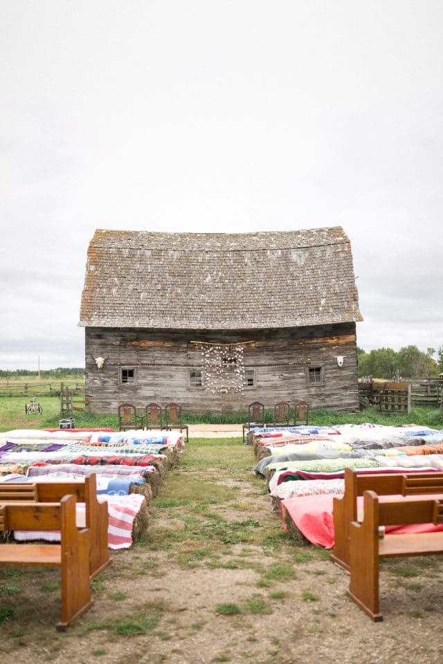 An old grey rustic barn with hay bales and blankets.