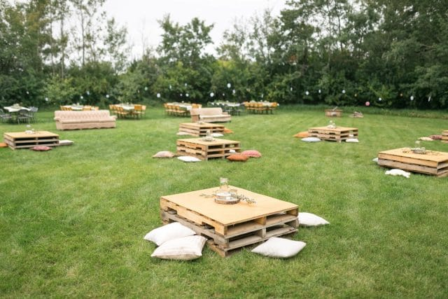 Tables made out of pallets sit in an open field surrounded by pillows.