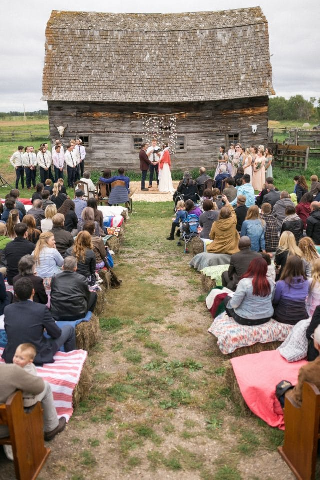 A bridal party stand in front of a barn as their guests look on.
