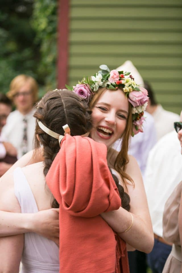 A bride laughs as she hugs her sister.