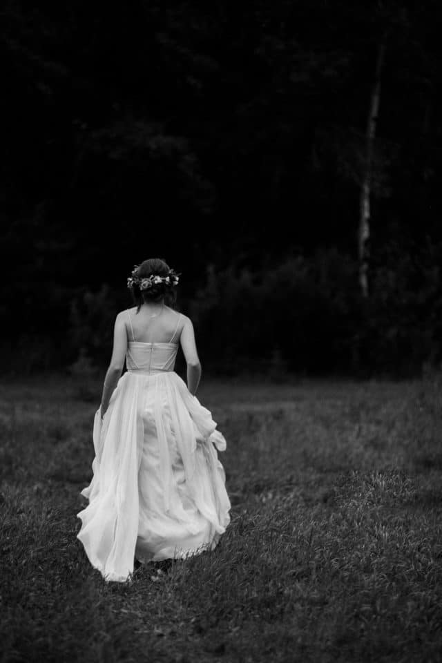 A bride walks away from camera in a black and white photo from Clint Bargen Photography.