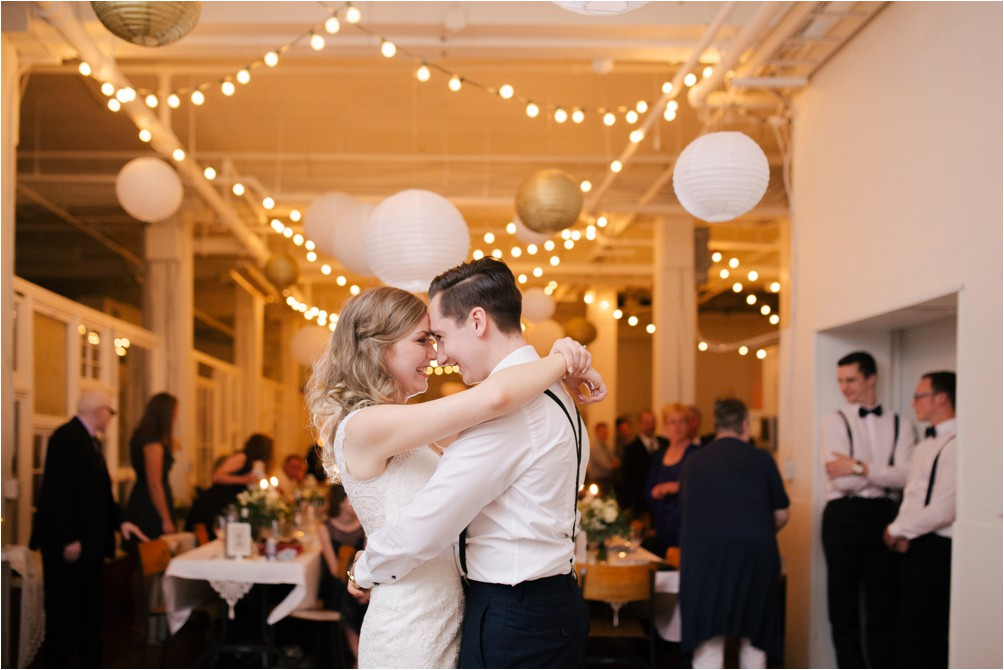 A bride and groom embrace as they share their first dance at 100 Braid Studios.