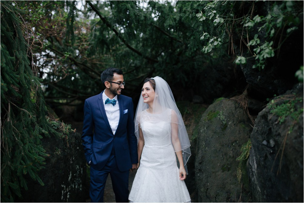 A couple walk in front of some rocks and trees at Van Dusen Gardens in Vancouver by Clint Bargen Photography.