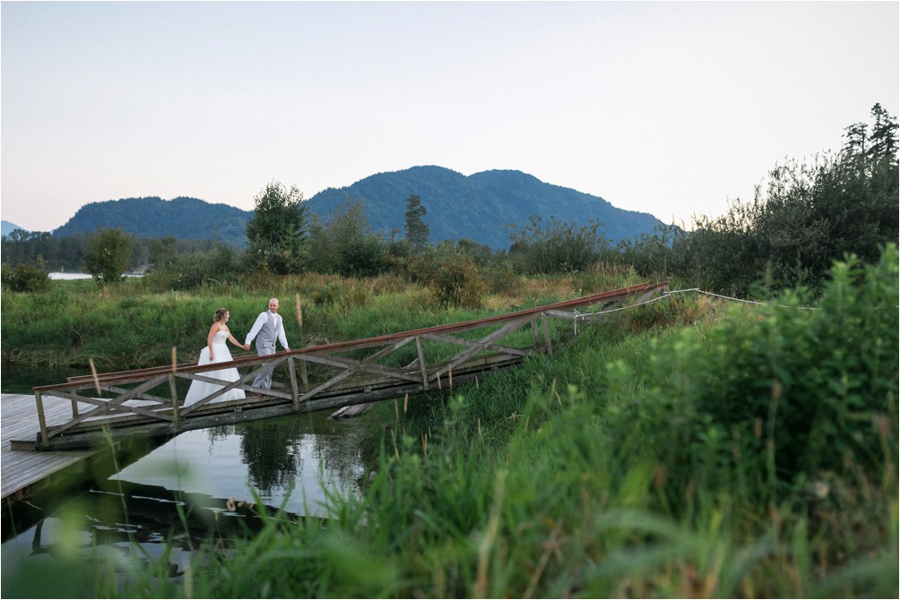 A wedding day couple walk up a dock near Rowena's Inn by The River.