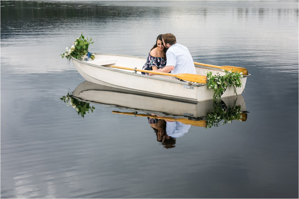 A couple kiss in a rowboat on Whonnock lake by Clint Bargen Photography.