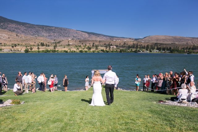 A bride walks with her father down the aisle towards the lake in Oliver, BC. Photo by Clint Bargen Photography.
