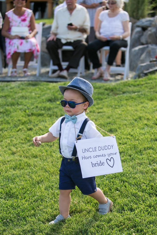 A kid wearing a fedora and sunglasses with a sign that reads