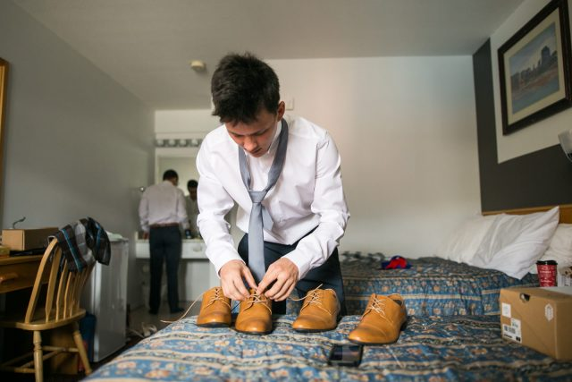 A groom ties his brown shoes from Call It Spring on a bed in Oliver, BC. Photo by Clint Bargen Photography.