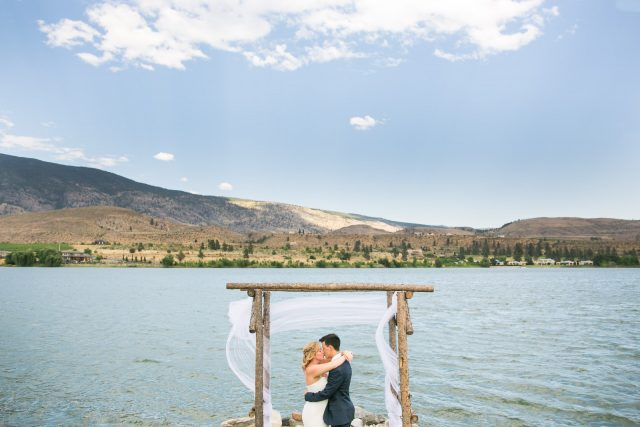 A bride and groom kiss in front of a lake in Oliver, BC. Photo by Clint Bargen Photography.