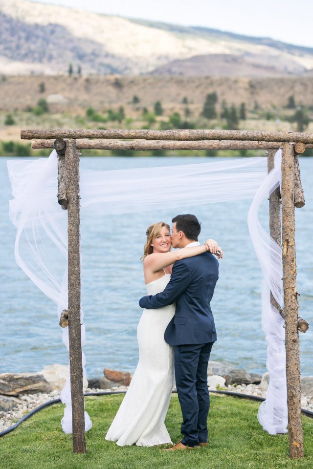 A groom kisses his bride on the cheek under a wooden arbor by a lake in Oliver, BC. Photo by Clint Bargen Photography.