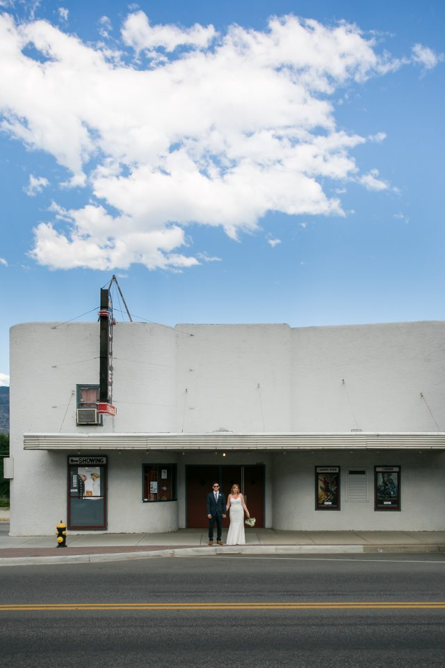 A bride and groom stand in front of the Oliver Movie Theatre at Covert Farms Winery near Oliver, BC. Photo by Clint Bargen Photography.