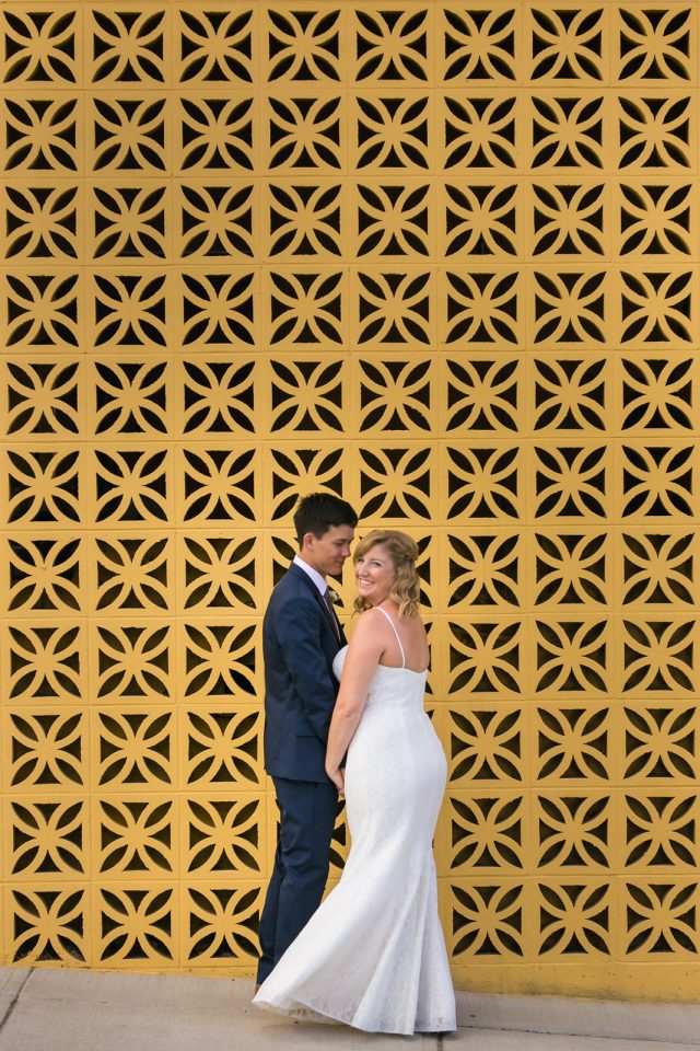 A bride and groom turn and laugh towards the camera in front of a yellow wall at Covert Farms Winery near Oliver, BC. Photo by Clint Bargen Photography.
