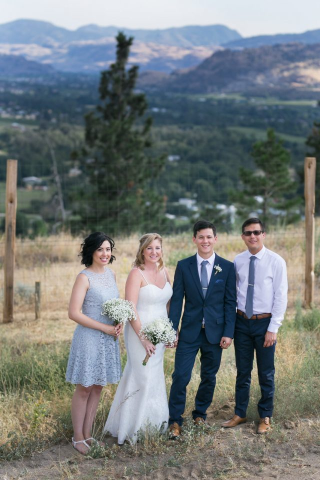 A wedding party stands with mountains behind them at Covert Farms Winery near Oliver, BC. Photo by Clint Bargen Photography.