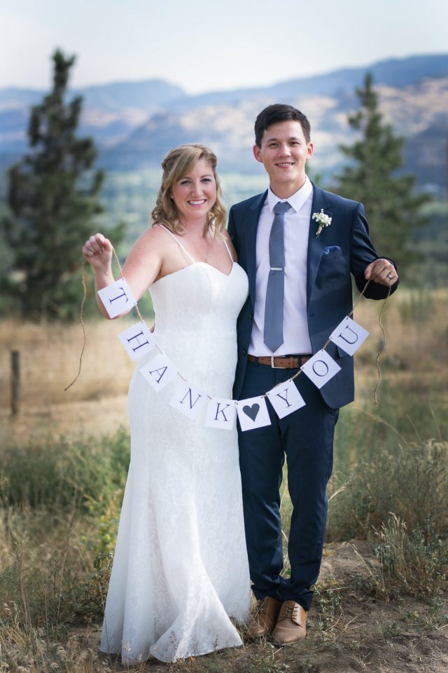 A bride and groom hold up a homemade