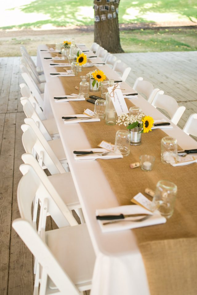 A wedding table decorated with sunflowers, mason jars and wine corks at Covert Farms Winery near Oliver, BC. Photo by Clint Bargen Photography.