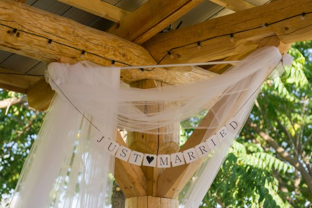 A just married sign hangs in front of a wooden beamed structure at Covert Farms Winery near Oliver, BC. Photo by Clint Bargen Photography.