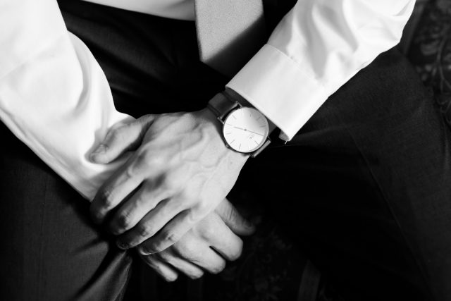 A black and white photo of a grooms hands wearing a watch in Oliver, BC. Photo by Clint Bargen Photography.
