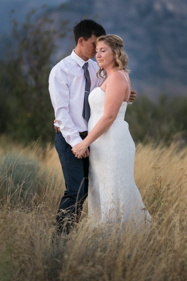 A bride and groom close their eyes and embrace in the tall grass in Oliver, BC. Photo by Clint Bargen Photography.