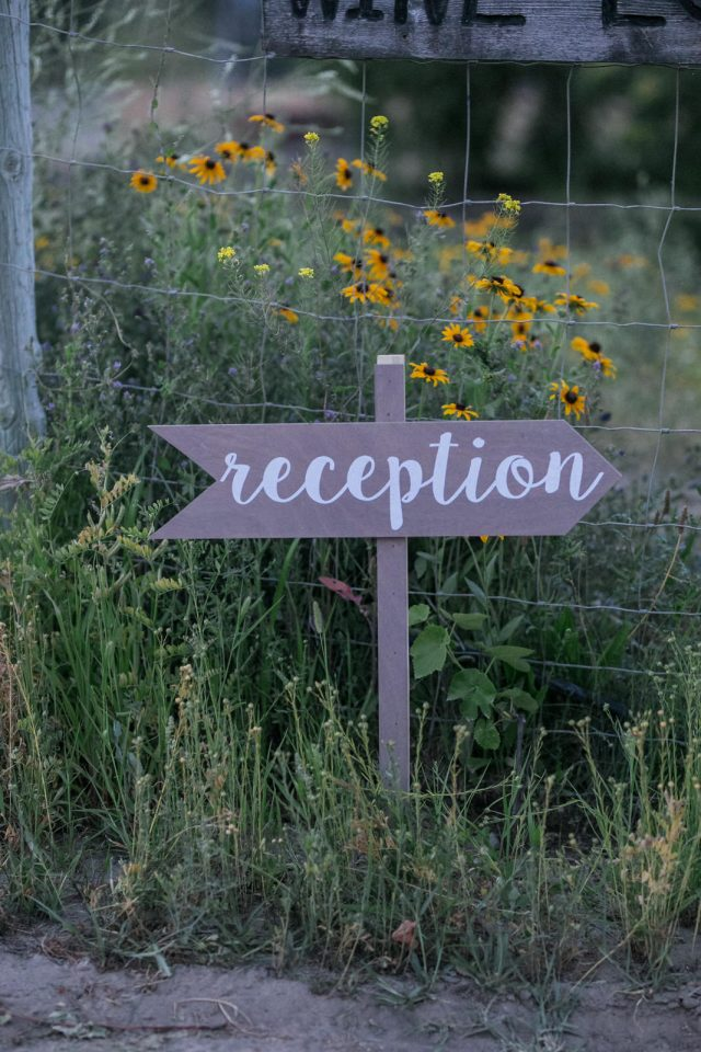 A wooden reception sign sits in the tall grass in front of some yellow flowers at Covert Farms Winery in Oliver, BC. Photo by Clint Bargen Photography.