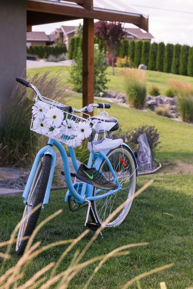 A blue bicycle decorated with running shoes and flowers sits on a lawn in Oliver, BC. Photo by Clint Bargen Photography.