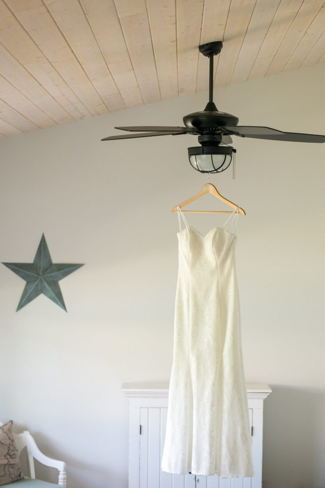 A white wedding dress hangs from a ceiling fan in a white room with a wooden ceiling in Oliver, BC. Photo by Clint Bargen Photography.