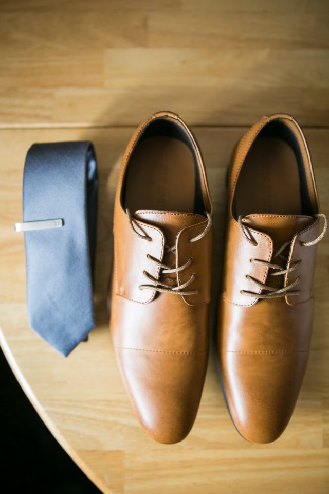 A close up shot of brown leather shoes and a rolled up blue tie in Oliver, BC. Photo by Clint Bargen Photography.