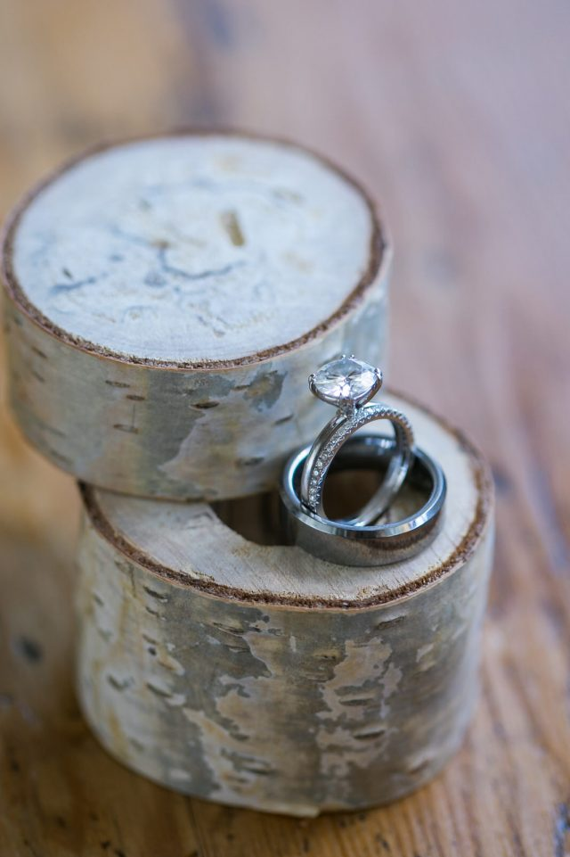 A close up shot of a wedding ring and a wooden poplar tree box in Oliver, BC. Photo by Clint Bargen Photography.