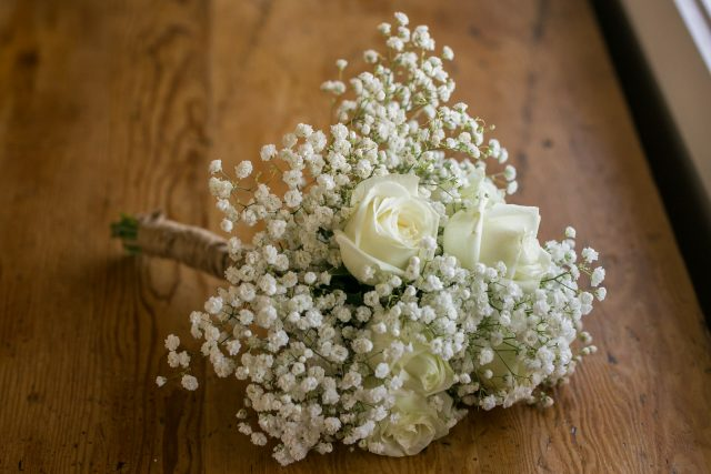 A close up shot of a wedding bouquet made of white roses and baby's breath in Oliver, BC. Photo by Clint Bargen Photography.