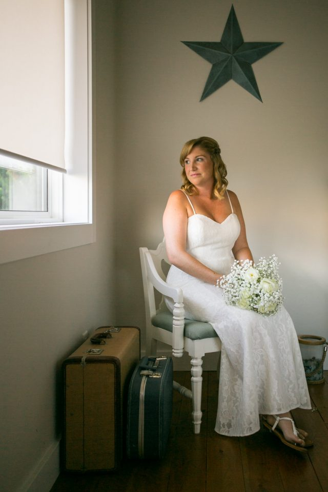 A bride signs in a white room with a star decoration above her head and suitcases beside her in Oliver, BC. Photo by Clint Bargen Photography.