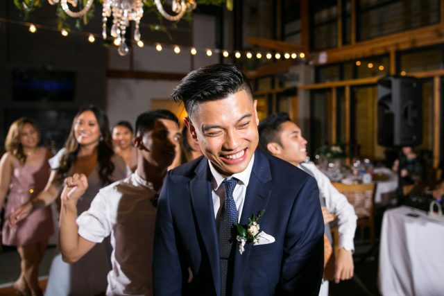 A groom smiles and looks down while dancing on his wedding day at Riverway Golf Course in Burnaby, BC.