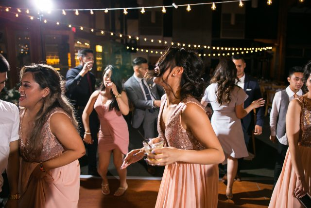 A wedding guests dances while holding a drink at Riverway Golf Course in Burnaby, BC.
