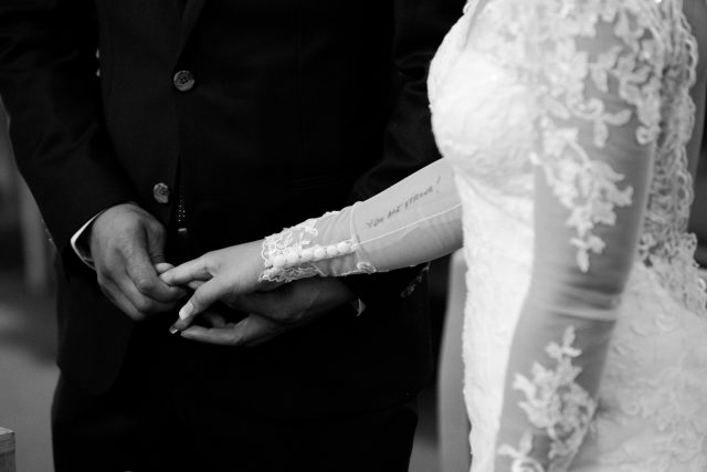 A close up shot of a bride's arm with a tattoo that reads