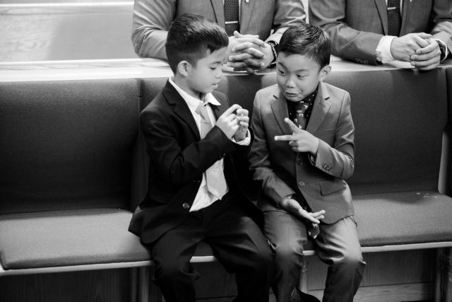 Two boys play paper, rock, scissors in the front row of the church at St. Mary's Parish in Burnaby, BC. Photo by Clint Bargen Photography.